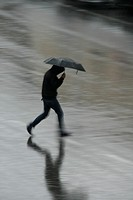 person with umbrella crossing road in rain