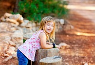 blond kid girl in tree trunk forest outdoor