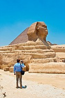 Tourist shooting video at Great Sphinx and Pyramid of Giza