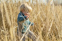 Toddler Boy Walking Through Tall Grass
