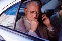Businessman using cell phone in back seat of car