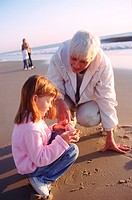 Grandmother explaining seashells to her granddaughter