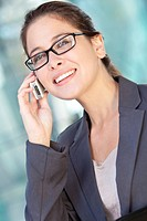 A beautiful smart young woman or businesswoman wearing glasses talking on cell phone in a sunny city location