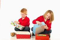 Curious children impatiently opening Christmas presents