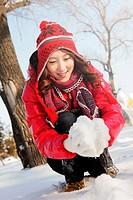 Woman in warm clothing making snowball