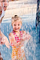 Mother and girl having fun under splashing water