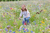 Portrait of smiling girl riding bicycle in wildflower field