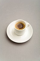 Image of porcelain cup with strong black coffee on white saucer