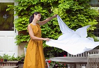 Woman spreading tablecloth in backyard