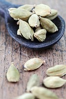 Dried cardamom pods with a wooden spoon