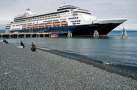 A cruise ship docked on the Homer Spit towering over sport fishermen on the beach of Kachemak Bay, Homer Spit, Southcentral Alaska, Spring