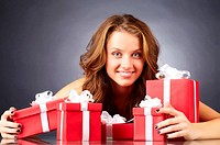 Portrait of a girl with giftboxes looking at camera and smiling
