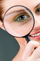 Close_up of young woman looking at camera through magnifying glass