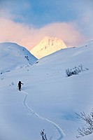Skiers skiing uphill above Thompson Pass on Girls Mountain near Valdez, Winter in Southcentral Alaska