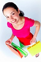 Portrait of young woman holding colorful paperbags