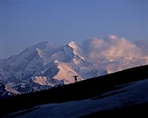 Man hikes along Highway Pass in hills near Mount McKinley at sunset, Denali National Park & Preserve, Interior Alaska, Summer