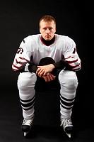 Portrait of healthy sportsman in hockey uniform on a black background