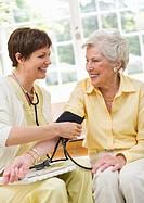 Nurse taking pulse of senior woman in nursing home