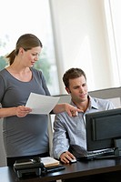 Young pregnant woman working with colleague in office