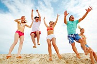 Photo of happy friends jumping on sandy beach on background of cloudy sky
