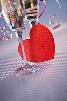 Flutes with champagne and red paper heart, close_up
