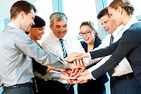 Photo of smiling co_workers making pile of hands and looking at camera