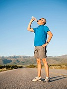 Mid adult an drinking water while taking break from running on empty road
