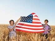Girls 10_11, 12_13 holding american flag in wheat field