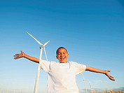 USA, Oregon, Wasco, Boy 8_9 standing in front wind turbine