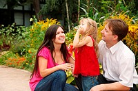 Parents observe as their daughter in red dress blows soap bubbles in summer garden.