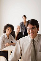 Smiling businessman looking at camera, business team in background