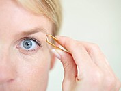 Mature woman using tweezer, close up