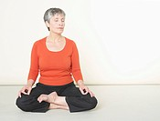 Senior woman doing meditation with eyes closed