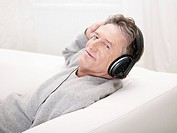 Germany, Hamburg, Senior man listening music, portrait
