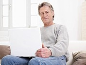 Germany, Hamburg, Senior man using laptop, portrait