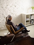 Germany, Hamburg, Senior woman sitting on chair and listening music