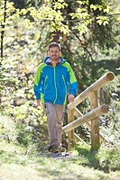 Germany, Upper Bavaria, Man hiking near railings, smiling, portrait