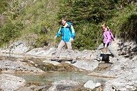 Germany, Upper Bavaria, Couple crossing stream while hiking