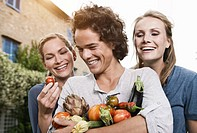 Italy, Tuscany, Magliano, Young man and women holding vegetables, smiling