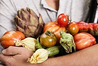 Italy, Tuscany, Magliano, Close up of young man holding different vegetables