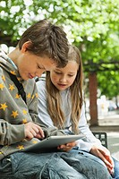 Germany, Berlin, Boy and girl using digital tablet