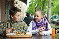 Germany, Berlin, Boy and girl eating pizza at cafe