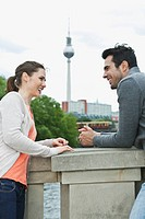 Germany, Berlin, Couple standing on bridge and talking