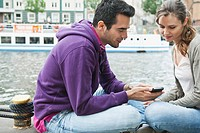 Germany, Berlin, Couple with cell phone on riverbank