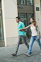 Germany, Berlin, Couple walking hand in hand through city street