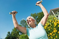 Germany, Bavaria, Senior woman doing exercise with dumbbell