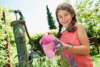 Germany, Bavaria, Girl gardening with watering can, smiling, portrait