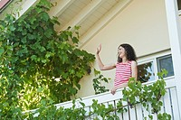 Germany, Bavaria, Woman waving from balcony, smiling