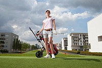 Germany, Bavaria, Munich, Young woman standing beside golf cart in city_golf ground