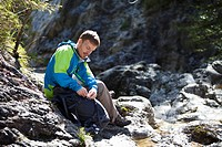 Germany, Upper Bavaria, Man sitting on rocks near stream